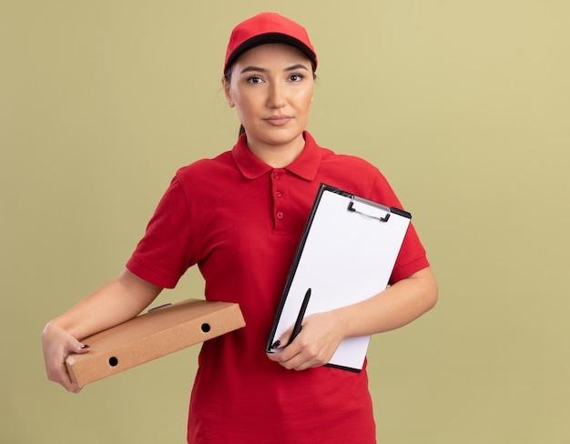 빨간 제복을 입은 젊은 배달 여자와 녹색 벽 위에 서있는 심각한 얼굴로 앞을보고 balnk 페이지와 피자 상자와 클립 보드를 들고 모자