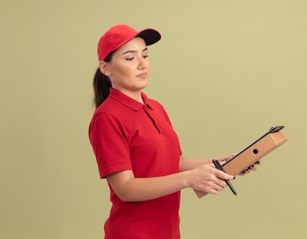 緑の壁の上に立って自信を持って見えるクリップボードと鉛筆でピザの箱を保持している赤い制服と帽子の若い配達の女性