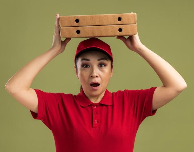 赤い制服を着た若い配達女性とピザの箱を持ったキャップが驚いて、緑の壁の上に立って驚いた