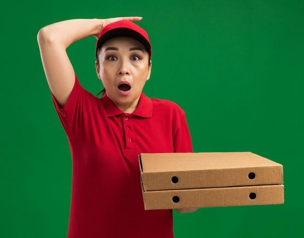 녹색 벽 위에 서있는 그녀의 머리에 손으로 깜짝 놀라게 빨간 유니폼과 모자를 들고 피자 상자에 젊은 배달 여자