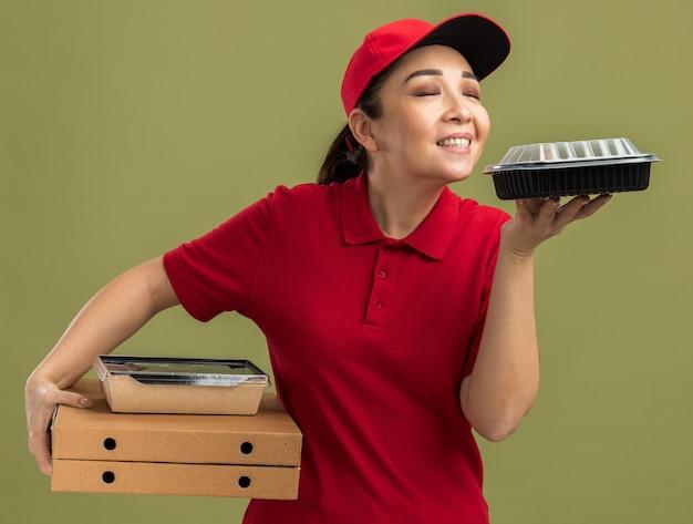 빨간 유니폼과 모자를 들고 피자 상자와 즐거운 향기를 흡입하는 음식 패키지에 젊은 배달 여자