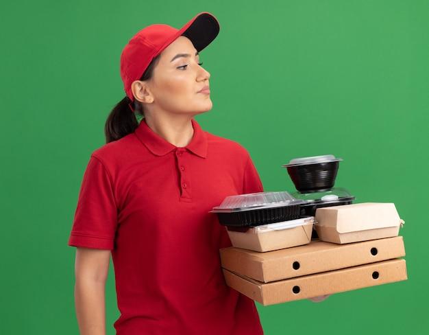 緑の壁の上に立っている真面目な顔で脇を見てピザの箱と食品パッケージを保持している赤い制服と帽子の若い配達の女性