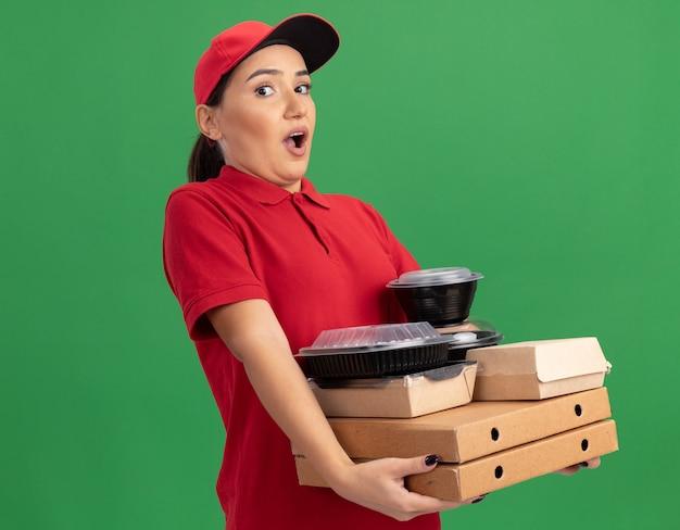 緑の壁の上に立って驚いて驚いた正面を見てピザの箱と食品パッケージを保持している赤い制服と帽子の若い配達の女性