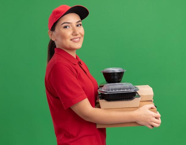 Молодая женщина-доставщик в красной форме и кепке держит коробки для пиццы и продуктовые пакеты, глядя вперед с улыбкой на лице, стоя над зеленой стеной