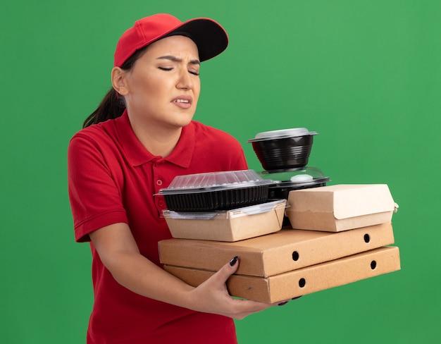 緑の壁の上に立って混乱して不機嫌そうに見えるピザの箱と食品パッケージを保持している赤い制服と帽子の若い配達の女性