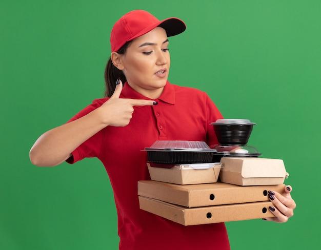 緑の壁の上に立って混乱している人差し指で指しているピザの箱と食品パッケージを保持している赤い制服と帽子の若い配達の女性