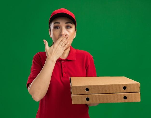 빨간 유니폼과 모자를 들고 젊은 배달 여자는 녹색 벽 위에 서있는 손으로 입을 덮고 충격을 받고 피자 상자를 들고