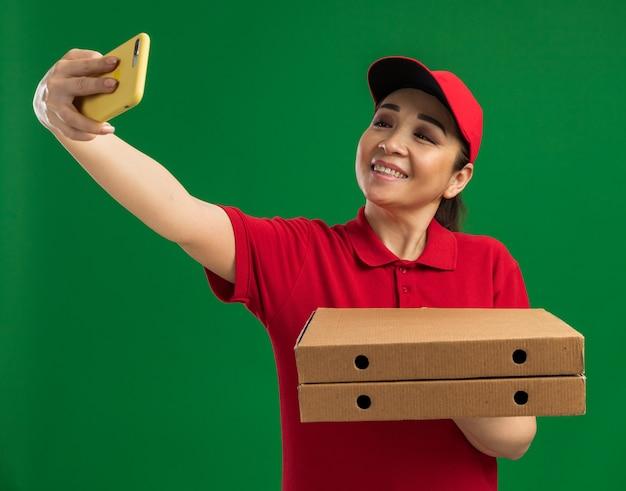빨간 제복을 입은 젊은 배달 여자와 모자는 녹색 벽 위에 유쾌하게 서있는 스마트 폰을 사용하여 셀카를하고 피자 상자를 들고