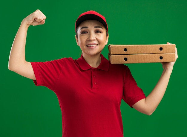 Молодая женщина-доставщик в красной форме и кепке держит коробки для пиццы на плече, поднимая кулак, счастливая и уверенная улыбка, стоя над зеленой стеной