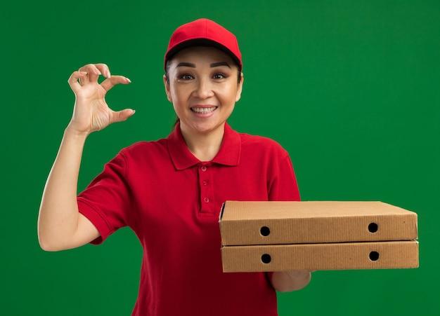 빨간 제복을 입은 젊은 배달 여자와 녹색 벽 위에 서있는 행복한 얼굴로 미소 짓는 작은 크기의 제스처를 보여주는 피자 상자를 들고 모자
