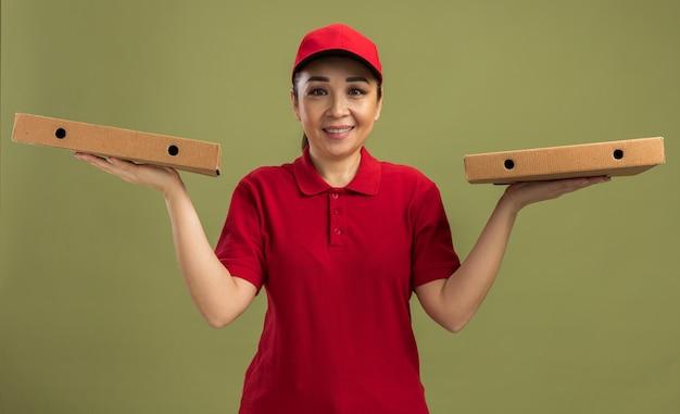 빨간 제복을 입은 젊은 배달 여자와 녹색 벽 위에 친절한 서 미소 피자 상자를 들고 모자