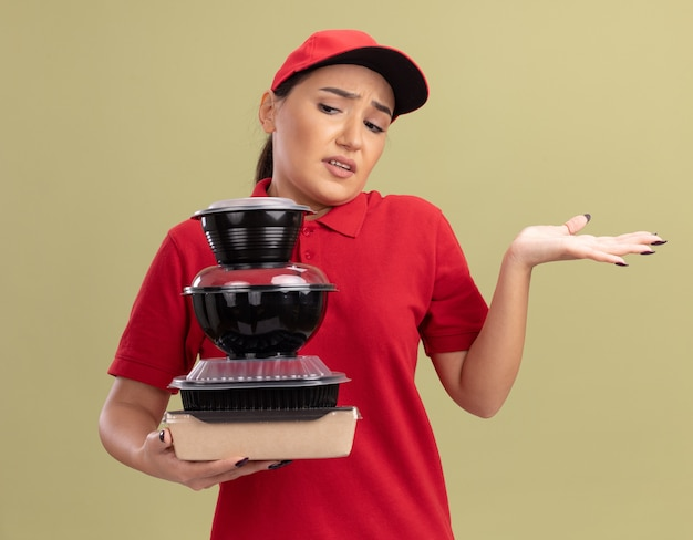 빨간색 제복을 입은 젊은 배달 여자와 녹색 벽 위에 서있는 대답이없는 혼란스럽고 불쾌한 음식 패키지 스택을 들고있는 모자