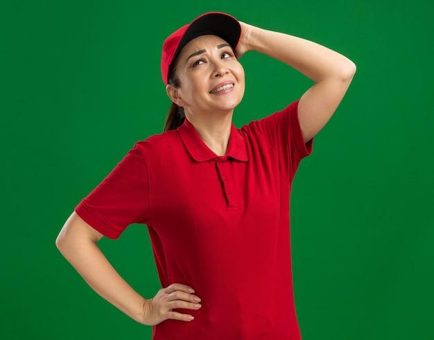 Молодая доставщица в красной форме и кепке смотрит вверх с растерянным выражением лица, касаясь ее головы, стоящей над зеленой стеной