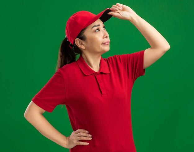 Молодая женщина-доставщик в красной форме и кепке смотрит вверх со скептическим выражением лица
