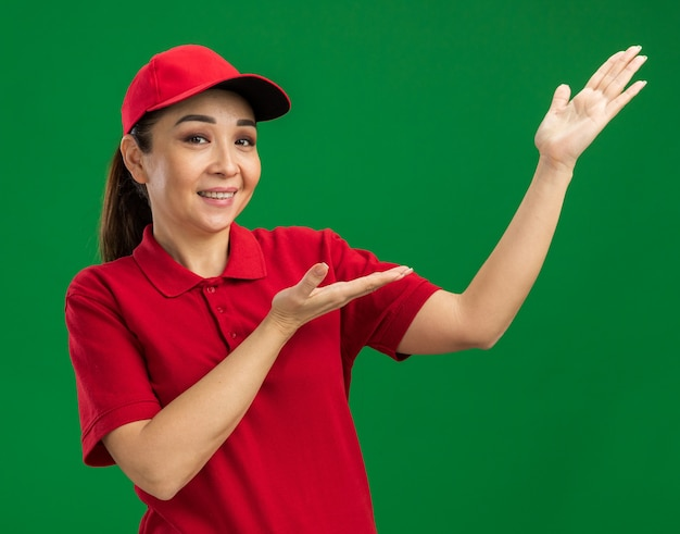 Молодая женщина-доставщик в красной форме и кепке, представляющая пространство для копирования с руками, счастливыми и позитивными, весело улыбаясь
