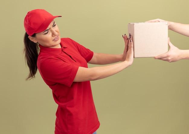 녹색 벽 위에 서있는 상자 패키지를 거부하는 빨간 유니폼과 모자에 젊은 배달 여자