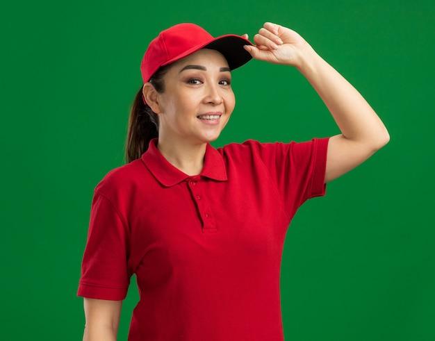 빨간 제복을 입은 젊은 배달 여자와 모자는 녹색 벽 위에 서있는 그녀의 모자를 만지고 자신감을 웃고