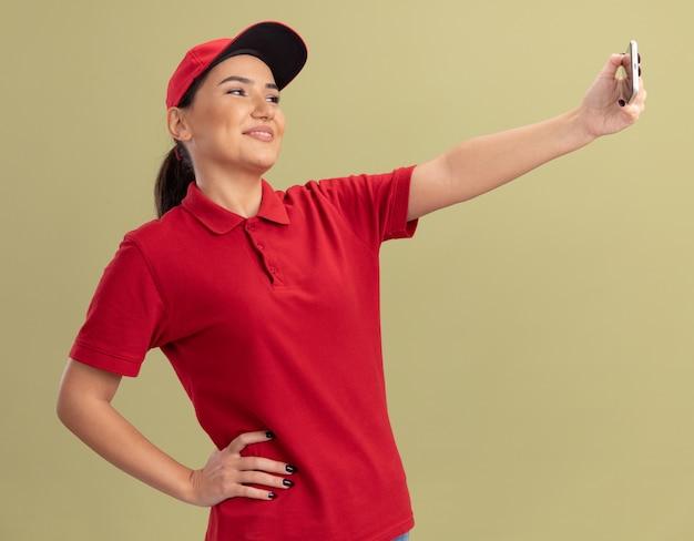 빨간 제복을 입은 젊은 배달 여자와 녹색 벽 위에 유쾌하게 서있는 셀카를하는 스마트 폰을 사용하는 모자