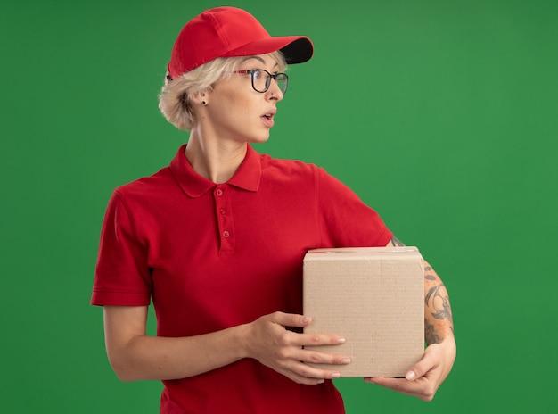 Молодая женщина-доставщик в красной форме и кепке в очках держит картонную коробку, глядя в сторону с растерянным выражением лица, стоя над зеленой стеной