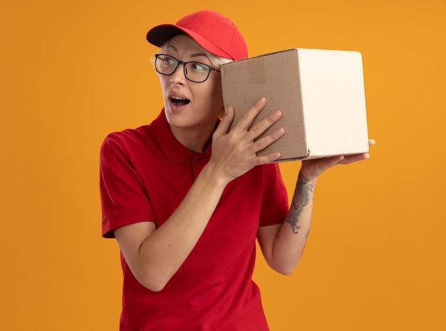 빨간 제복을 입은 젊은 배달 여자와 오렌지 벽 위에 서있는 그녀의 귀에 골판지 상자를 들고 안경을 쓰고 모자