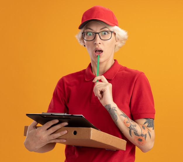 빨간 제복을 입은 젊은 배달 여자와 피자 상자와 클립 보드와 연필을 들고 안경을 쓰고 모자를 쓰고 걱정하고 오렌지 벽 위에 서서 혼란스러워합니다.