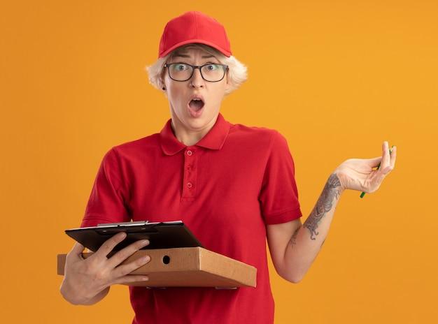 빨간 제복을 입은 젊은 배달 여자와 연필로 피자 상자와 클립 보드를 들고 안경을 쓰고 모자를 쓰고 놀란다.