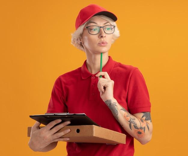 빨간 제복을 입은 젊은 배달 여자와 오렌지 벽 위에 서있는 심각한 얼굴로 옆으로 연필 lookign으로 피자 상자와 클립 보드를 들고 안경을 쓰고 모자