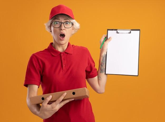 빨간 제복을 입은 젊은 배달 여자와 클립 보드를 보여주는 피자 상자를 들고 안경을 쓰고 모자를 쓰고 놀라게하고 오렌지 벽 위에 서있는 걱정