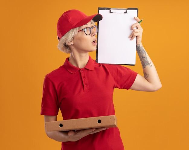 빨간 제복을 입은 젊은 배달 여자와 그것을보고 클립 보드를 보여주는 피자 상자를 들고 안경을 쓰고 모자 오렌지 벽 위에 서 흥미