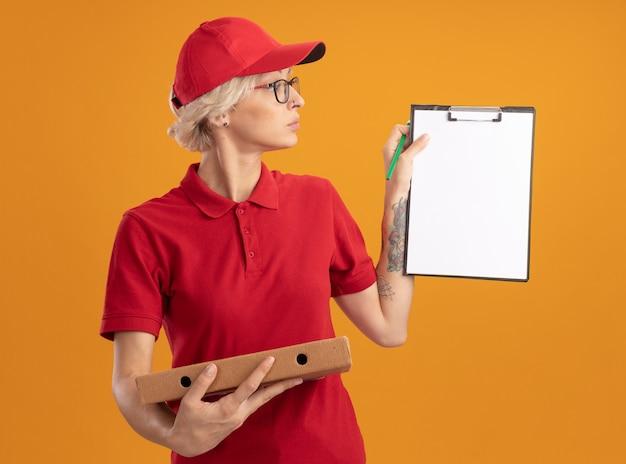 빨간 제복을 입은 젊은 배달 여자와 오렌지 벽 위에 서있는 심각한 얼굴로보고 클립 보드를 보여주는 피자 상자를 들고 안경을 쓰고 모자