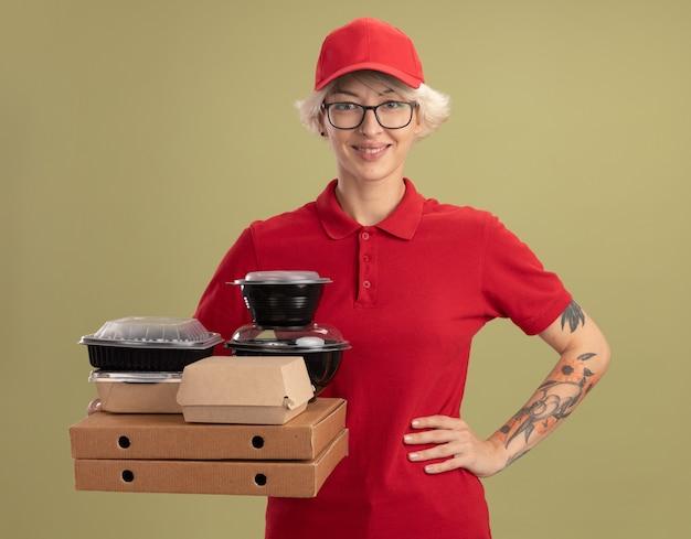 빨간 제복을 입은 젊은 배달 여자와 모자를 쓰고 피자 상자와 녹색 벽 위에 서있는 엉덩이에 팔로 자신감이 웃는 음식 패키지를 들고 모자