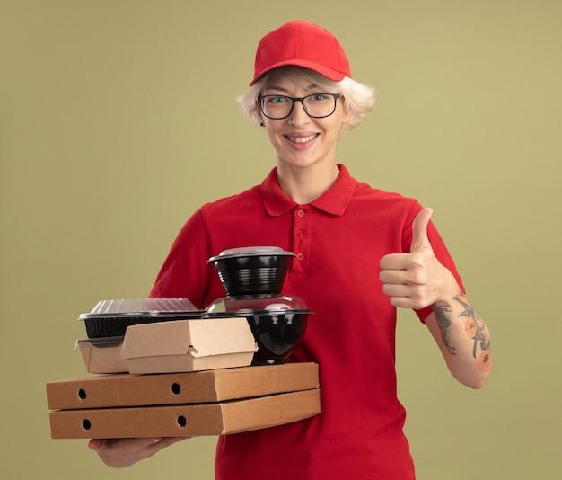 Молодая женщина-доставщик в красной форме и кепке в очках держит коробки для пиццы и продуктовые пакеты, улыбаясь счастливым лицом, показывая пальцы вверх, стоя над зеленой стеной