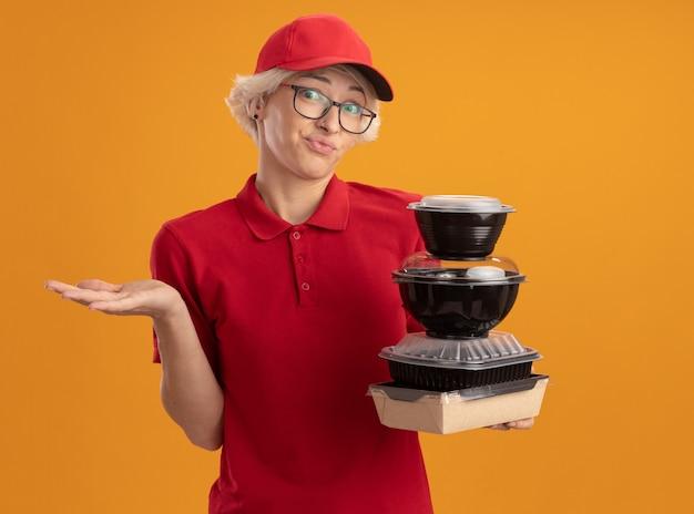 Молодая женщина-доставщик в красной форме и кепке в очках держит стопку продуктовых пакетов, выглядя смущенной с поднятой рукой, стоя над оранжевой стеной