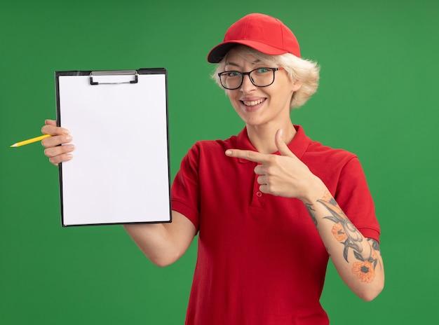 赤い制服とキャップを身に着けている若い配達の女性は、空白のページと鉛筆が緑の壁の上に元気に立って笑っているクリップボードに人差し指で指しているクリップボードを示しています