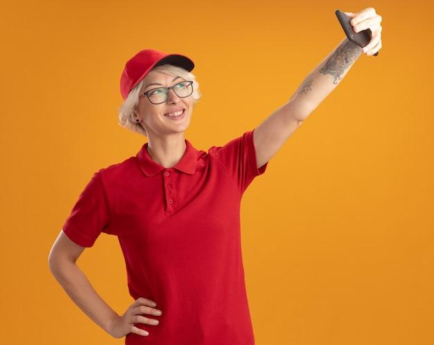 オレンジ色の壁の上に元気に立って自分撮りをしているスマートフォンを使用して眼鏡をかけている赤い制服と帽子の若い配達女性