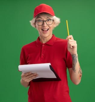 赤い制服とキャップを身に着けている若い配達の女性は、空白のページと鉛筆で眼鏡をかけて、緑の壁の上に立っている新しいアイデアを持って幸せで興奮しています