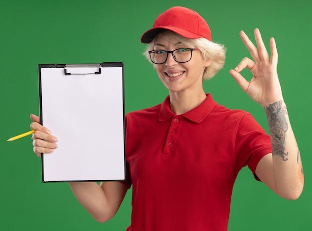 Молодая женщина-доставщик в красной форме и кепке в очках с буфером обмена с пустыми страницами и карандашом, весело улыбаясь, показывая знак ок, стоящий над зеленой стеной