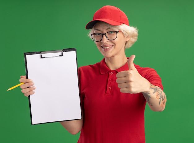 빨간색 제복을 입은 젊은 배달 여자와 빈 페이지와 연필 클립 보드와 안경을 쓰고 녹색 벽 위에 서있는 엄지 손가락을 유쾌하게 보여주는 미소