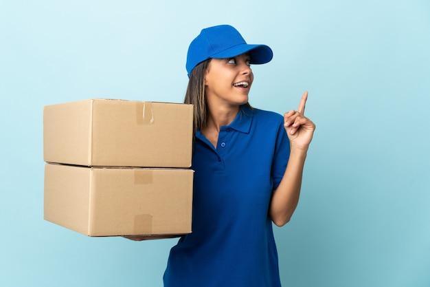 Молодая женщина-доставщик, изолированная на синем, намеревается понять решение, поднимая палец вверх