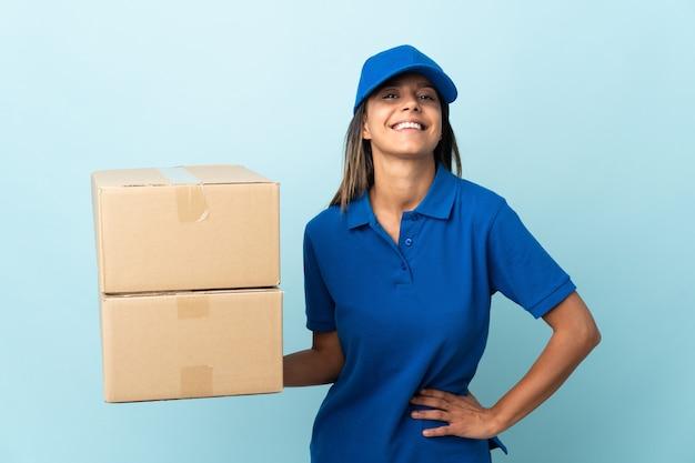 엉덩이에 팔을 포즈와 미소 파란색 벽에 고립 된 젊은 배달 여자
