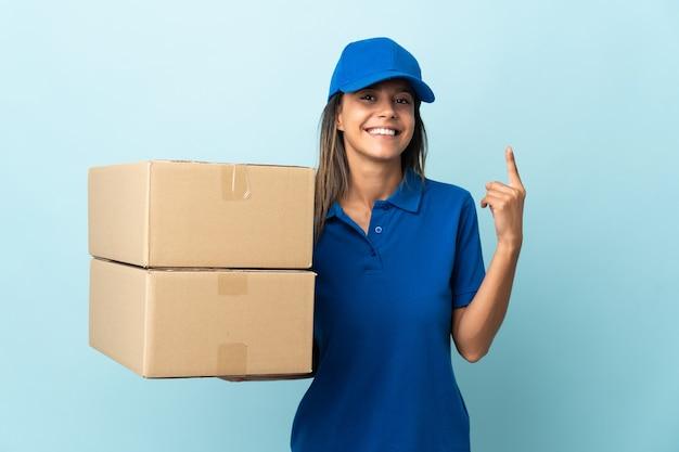 Молодая женщина-доставщик изолирована на синей стене, показывая и поднимая палец в знак лучших