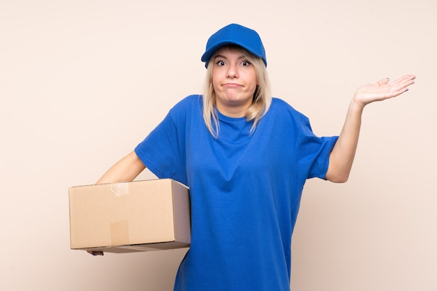 Young delivery woman over isolated wall having doubts with confuse face expression