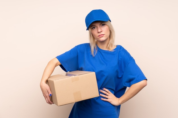 Young delivery woman over isolated wall keeping arms crossed