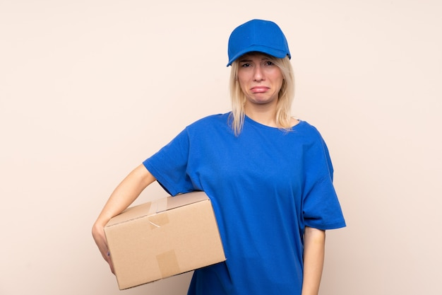 Young delivery woman over isolated wall sad