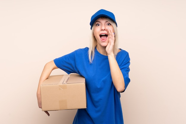 Young delivery woman over isolated wall shouting with mouth wide open