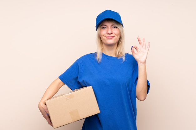 Young delivery woman over isolated wall showing an ok sign with fingers