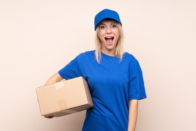 Young delivery woman over isolated wall with surprise facial expression