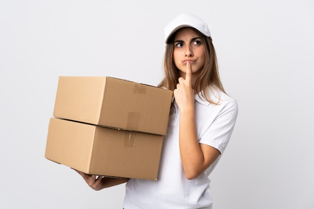 Young delivery woman over isolated white background having doubts while looking up