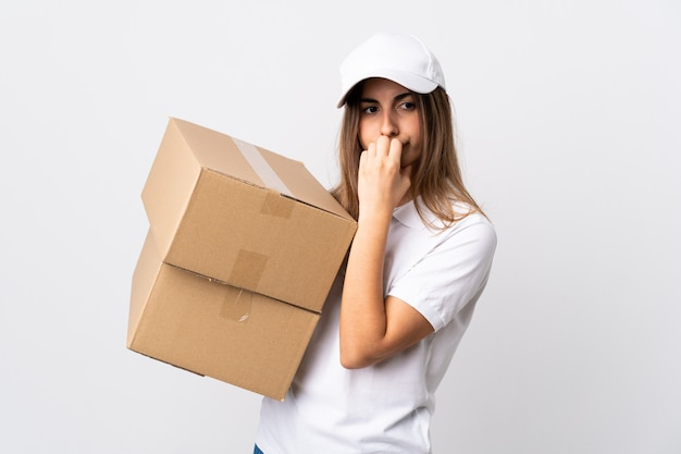 Young delivery woman over isolated white background having doubts