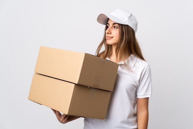 Young delivery woman over isolated white background looking to the side
